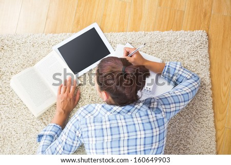 Brunette female student lying on the floor doing assignments using her tablet - stock photo