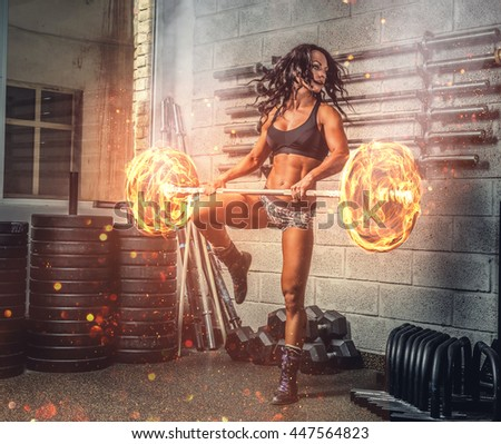 Brunette fitness woman exercising with burning barbell in a gym club. - stock photo