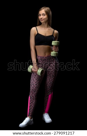 Brunette fitness woman with dumbbells. Isolate in studio on a black background. - stock photo