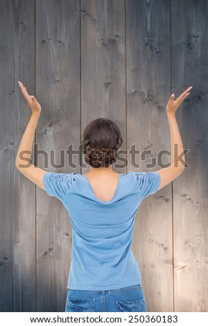Brunette gesturing against bleached wooden planks background - stock photo