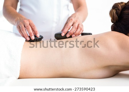 Brunette getting hot stone massage in a healthy spa - stock photo