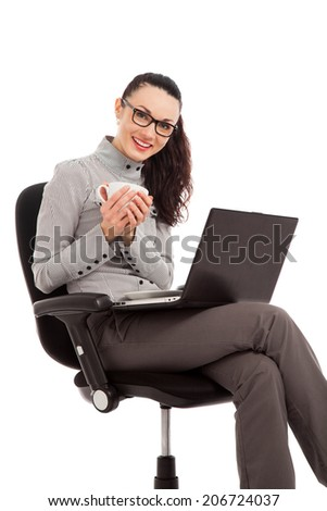 brunette girl drinking coffee, sitting in the chair with laptop over white background - stock photo