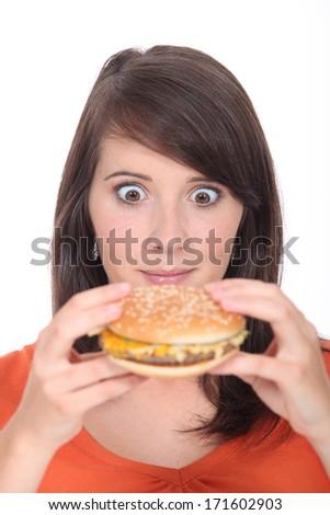 Brunette girl eating Burger - stock photo