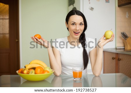brunette girl holding fruits sitting in the kitchen and drink juice - stock photo
