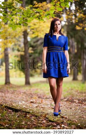 Brunette girl in blue dress walking at park. - stock photo