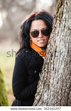 Brunette girl in coat and sunglasses in a forest. - stock photo