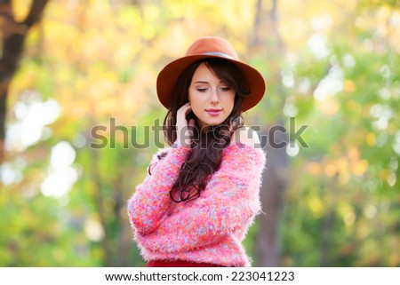 Brunette girl in pink sweater in the autumn park. - stock photo