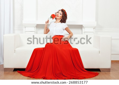 Brunette girl sitting on a white sofa with a flower in her hand and smiling. - stock photo