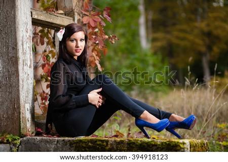 Brunette girl sitting on overgrown stairs. - stock photo