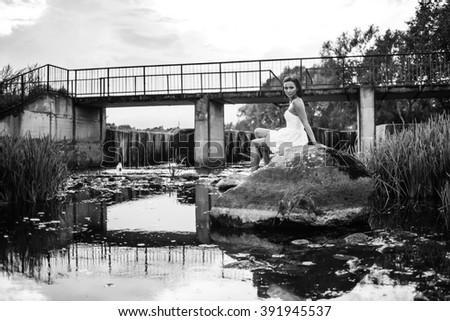 Brunette girl sitting on stone. - stock photo