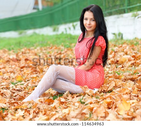 brunette girl sitting on the autumn leaves - stock photo