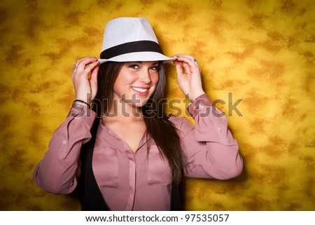 brunette girl smiling and wearing a white fedora hat - stock photo