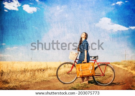 Brunette girl  with  bycicle and suitcase on country side road. - stock photo