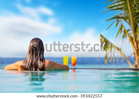 Brunette girl with cocktails in swimming pool - stock photo