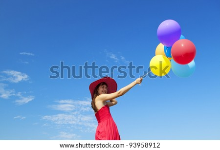 Brunette girl with colour balloons at blue sky background. - stock photo