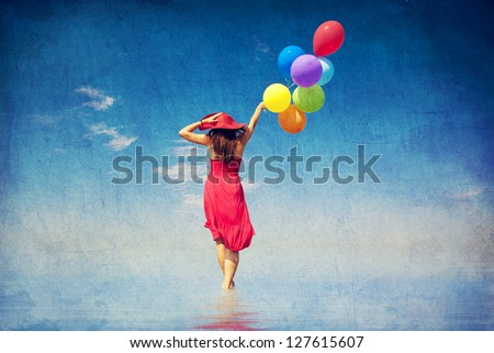 Brunette girl with colour balloons at coast. Photo in old color image style. - stock photo