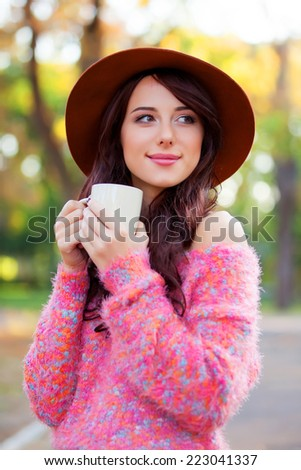 Brunette girl with cup of coffee in the autumn park. - stock photo