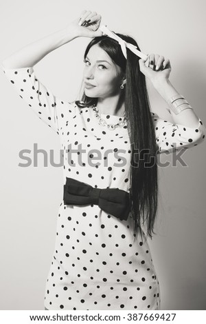 Brunette glamour beautiful pinup woman in a white dress with polka dot, long hair looking surprised on white background portrait black and white image - stock photo