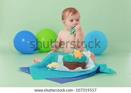 Brunette hair blue eyed baby boy eating and tasting the icing of his ocean themed birthday cupcake with orange fish and seaweed while sitting on green background with green and blue balloons behind - stock photo
