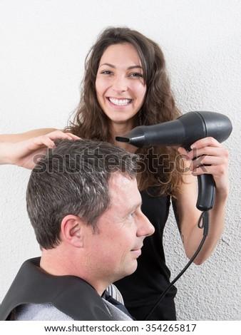 Brunette hairdresser drying her customer's hair in her salon - stock photo