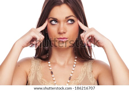 Brunette holding fingers on her temples and thinking - stock photo