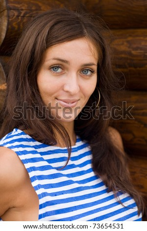 Brunette in a striped shirt on the background wall of wood - stock photo