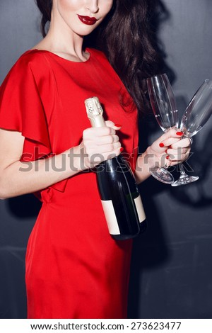 brunette in red dress with bottle of champagne and two glasses - stock photo