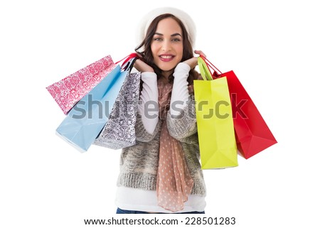 Brunette in winter clothes with shopping bags on white background - stock photo