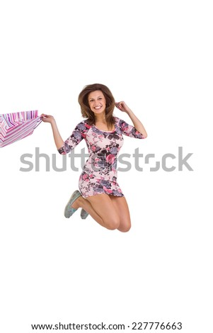 Brunette jumping while holding shopping bags on white background - stock photo