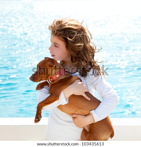 brunette kid girl with dog on the sea view from a boat - stock photo