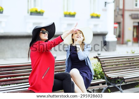 Brunette lady shows something to the blonde - stock photo