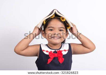 Brunette little girl with a book on her head isolated on a  white background - stock photo