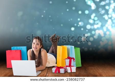 Brunette lying and using her laptop against shimmering light design over boards - stock photo