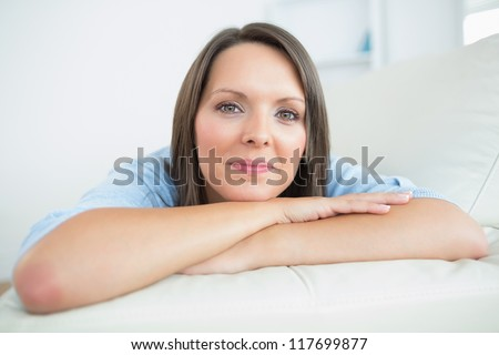 Brunette lying on couch smiling leaning on arms - stock photo