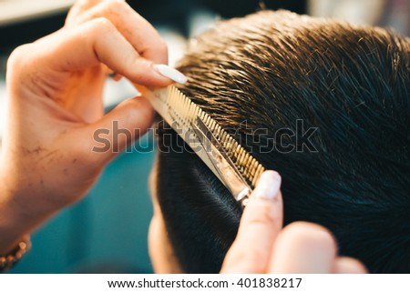 Brunette man getting a haircut by a professional hairdresser using comb and grooming scissors. Closeup view with shallow depth of field.   - stock photo