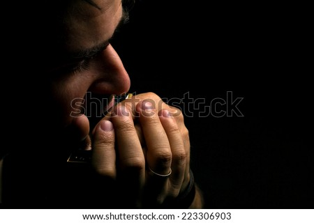 brunette man playing on harmonica on dark background with place for your text - stock photo