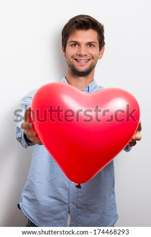 Brunette man wearing a blue shirt and holding a red heart balloon - stock photo