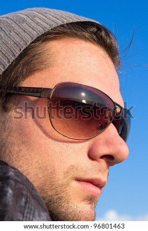 Brunette Man With Sunglasses And A Hat Looking Into The Blue Sky - stock photo