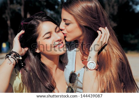 brunette model girl kissing and smile her lovely best friends. outdoors - stock photo