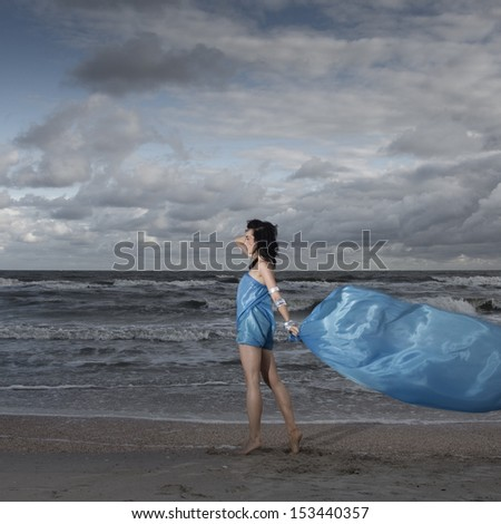 Brunette model standing on sea shore with long flag material - stock photo