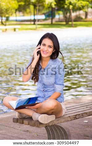 Brunette model wearing denim shirt and white shorts relaxing in park environment, sitting on bench next to lake using phone. - stock photo