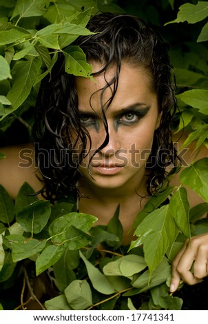 Brunette model with dark eye makeup and wet hair on a bright day - stock photo