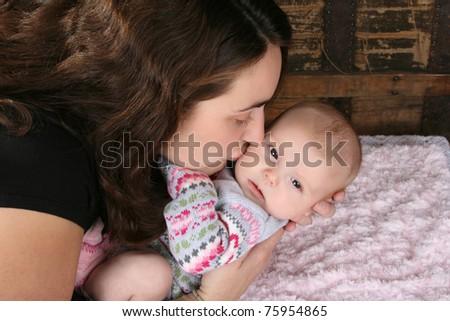 Brunette mother lovingly holding her baby girl - stock photo