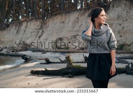 brunette on sea coast in autumn wearing grey pullover - stock photo