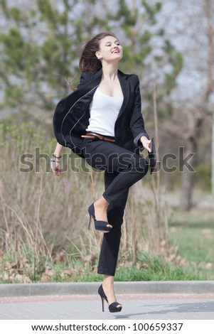 Brunette on stiletto heels in the park. Happy young woman in black suit runs along the park - stock photo