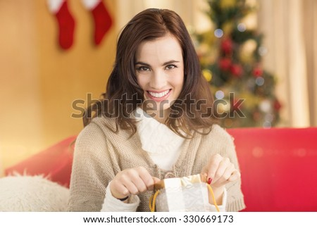 Brunette opening a gift on the couch at christmas at home in the living room - stock photo