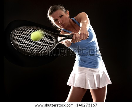 brunette playing tennis on black background - stock photo