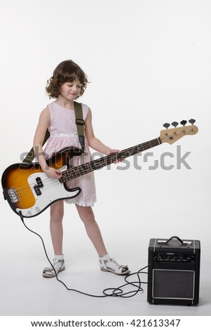 Brunette plays the guitar with cute smile on her face. Talanted child looks on the musical instrument connected to its amp. White background in the studio. - stock photo