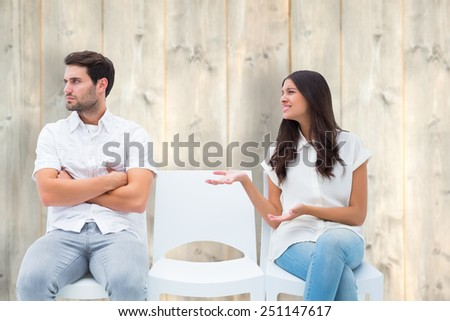 Brunette pleading with angry boyfriend against pale wooden planks - stock photo