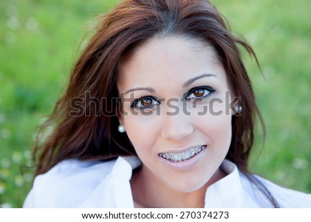 Brunette pretty woman with brackets relaxing in the park - stock photo